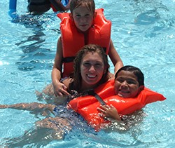Woman smiling with 2 children wearing life jackets in the pool